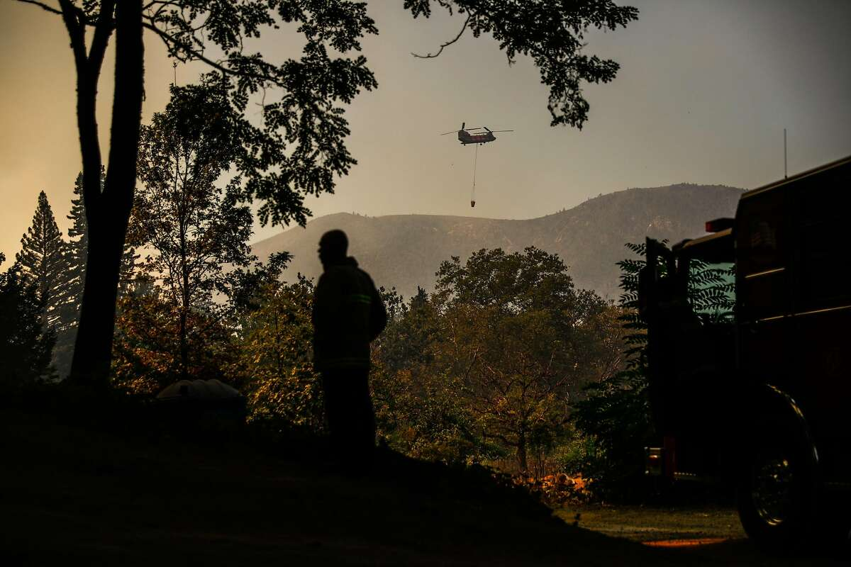 A firefighter stands by as a helicopter makes drops over the Glass Fire on Sunday, Oct. 4, 2020 in Calistoga, California. Cool weather the Bay Area pleaded for as it sweated through last week is here, but the hoped-for weekend rain is unlikely to arrive, dashing hopes that Mother Nature might chip in toward the ongoing firefights across Northern California.