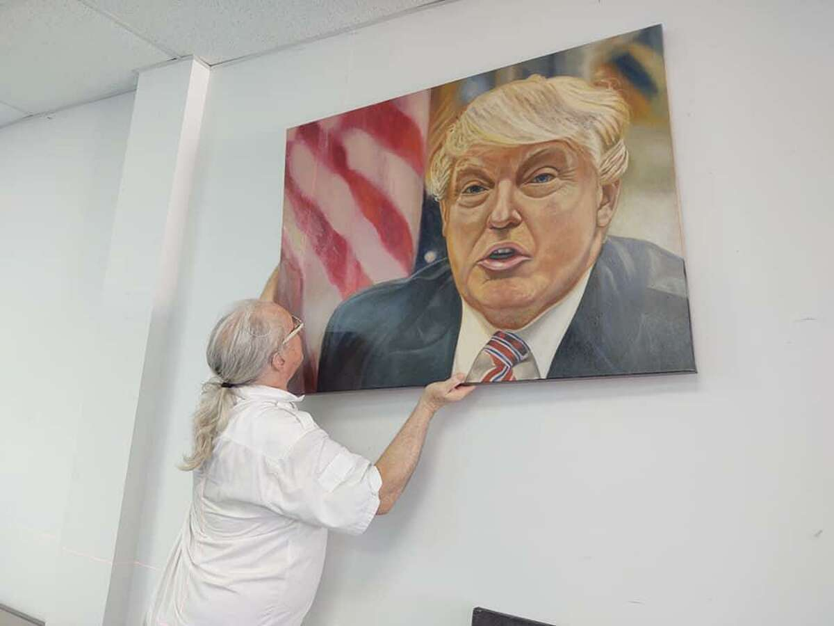 Bruce Badeau hangs a portrait of President Donald Trump at the new Trump art gallery in Katy.