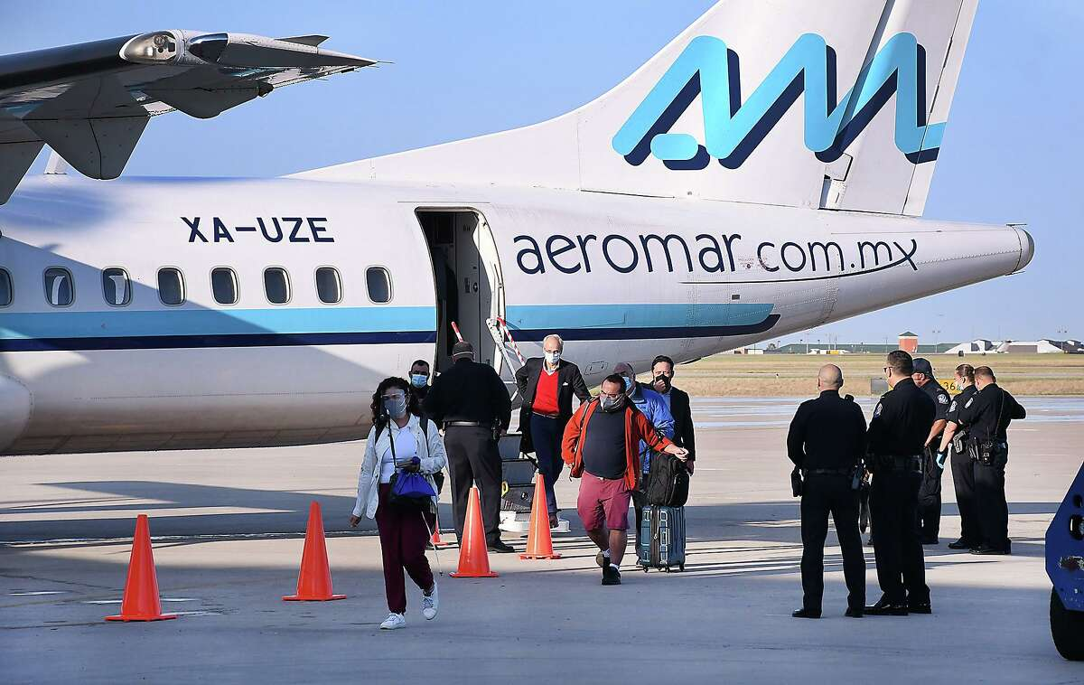 U.S. Customs agents stand by as passengers exit the airplane for the inaugural flight for AeroMar at the Laredo International Airport, Monday, October 5, 2020. The airline will offer flights to Mexico City.