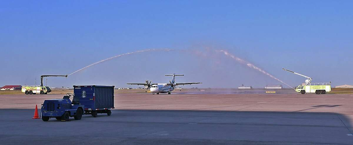 A pair of Laredo Fire Department pumper trucks spray an arch of water as the inaugural flight for AeroMar lands at the Laredo International Airport, Monday, October 5, 2020. The airline will offer flights to Mexico City.