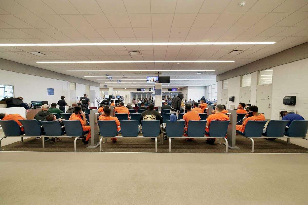 Detainees and inmates wait in the waiting room at the Harris County Joint Processing Center where bail hearings take place on Thursday, Mar. 5, 2020 in Houston.
