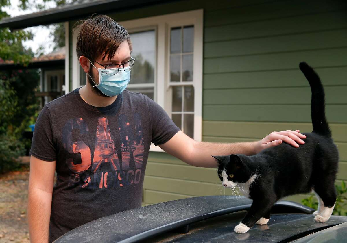 Bobby Hougen pets his cat Athena at home in Santa Rosa, Calif. on Thursday, Oct. 1, 2020. Hougen has grown tired of always being on alert and ready to evacuate after years of wildfires and is planning to move out of the area.