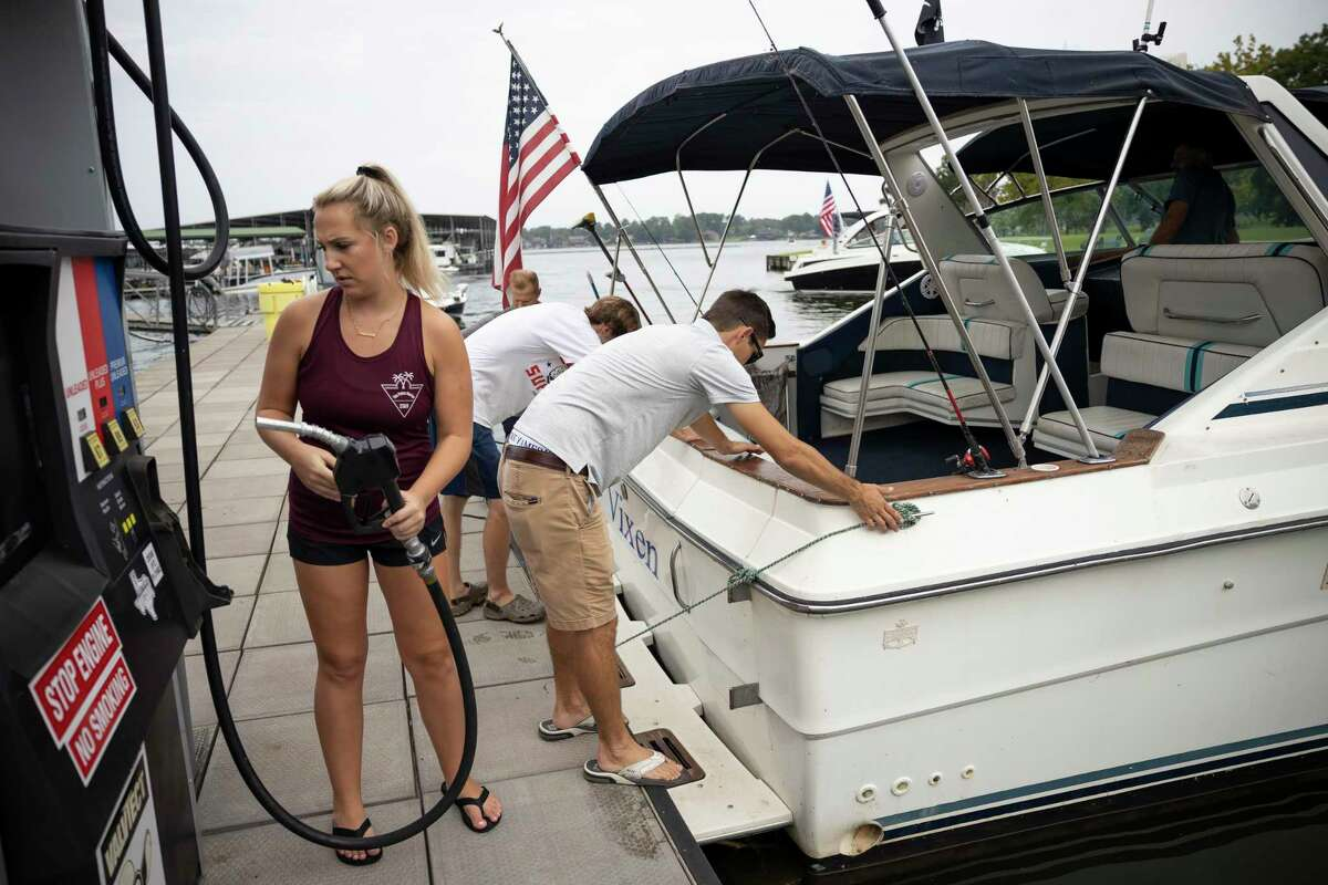 Lindsay King, manager of the Palms Marina, fills a visitors gas tank at Lake Conroe, Saturday, Sept. 5, 2020. Due to the COVID-19 pandemic the 21,000-acre lake has seen a huge increase in visitors after most businesses were forced to shut down.