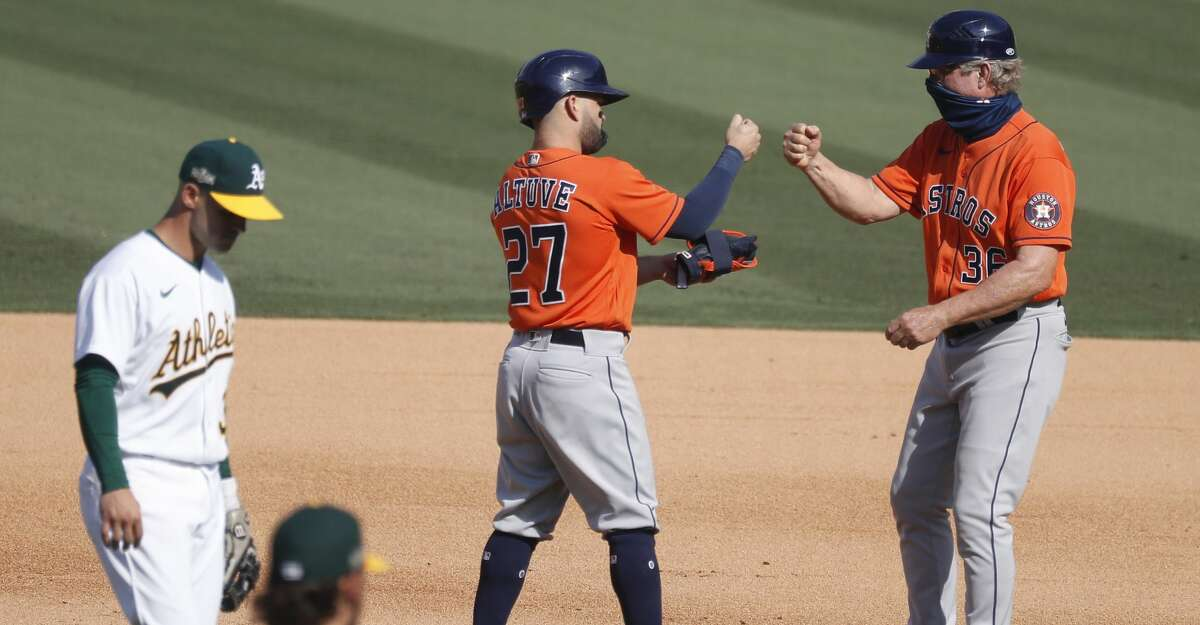 Houston Astros Jose Altuve celebrates his RBI double with first base coach Chris Speier during the sixth inning of Game 1 of the American League Division Series, Monday, October 5, 2020, in Los Angeles, at Dodger Stadium.