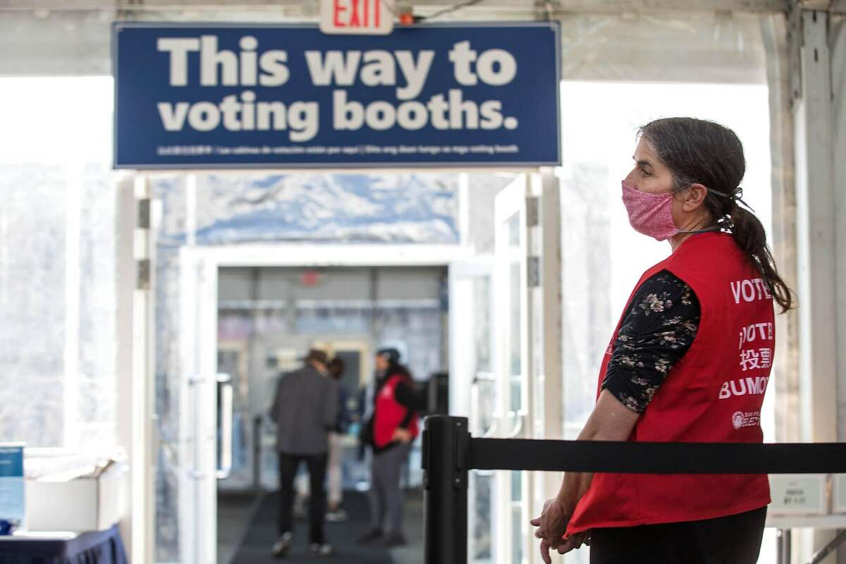 Jenny Stanley guides people to voting booths on the first day of early, in-person voting outside Bill Graham Civic Auditorium in San Francisco on Monday.