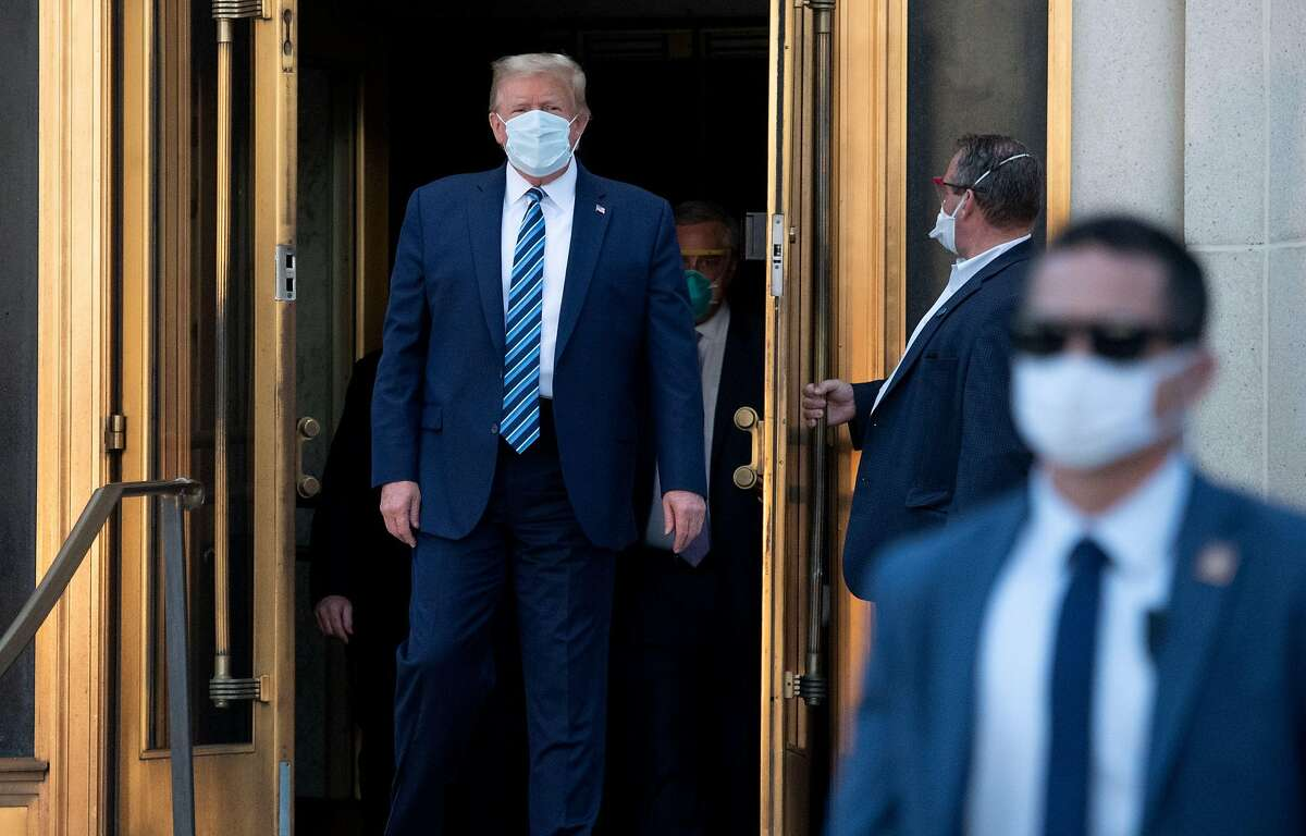 """US President Donald Trump walks out of Walter Reed Medical Center in Bethesda, Maryland before heading to Marine One on October 5, 2020, to return to the White House after being discharged. - Trump announced he would be """"back on the campaign trail soon"""", just before returning to the White House from a hospital where he was being treated for Covid-19. (Photo by SAUL LOEB / AFP) (Photo by SAUL LOEB/AFP via Getty Images)"""