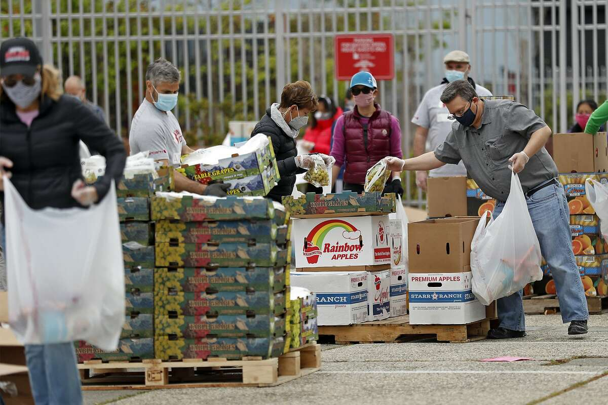 Volunteers assemble some of 1600 food bags that SF-Marin Food Bank distributes at a pop-up pantry at Bayview Opera House in San Francisco, Calif., on Monday, April 20, 2020.