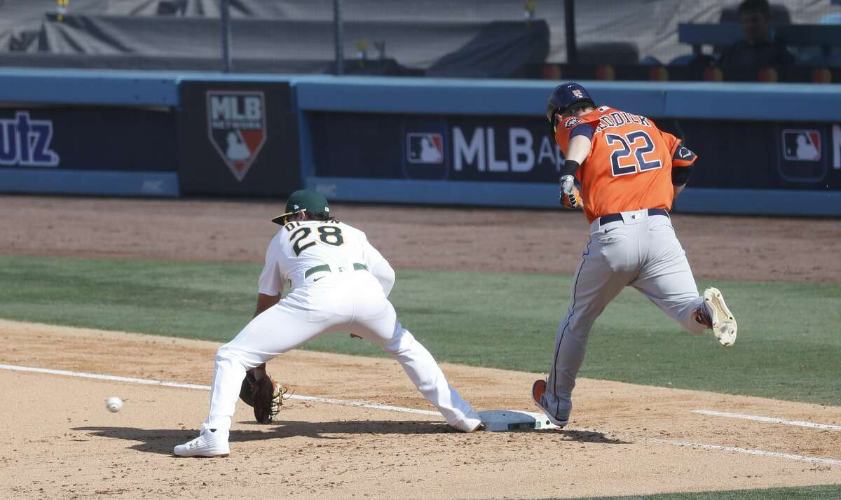 Houston Astros Josh Reddick reaches first base on a fielding error by Oakland Athletics shortstop Marcus Semien during the sixth inning of Game 1 of the American League Division Series, Monday, October 5, 2020, in Los Angeles, at Dodger Stadium.