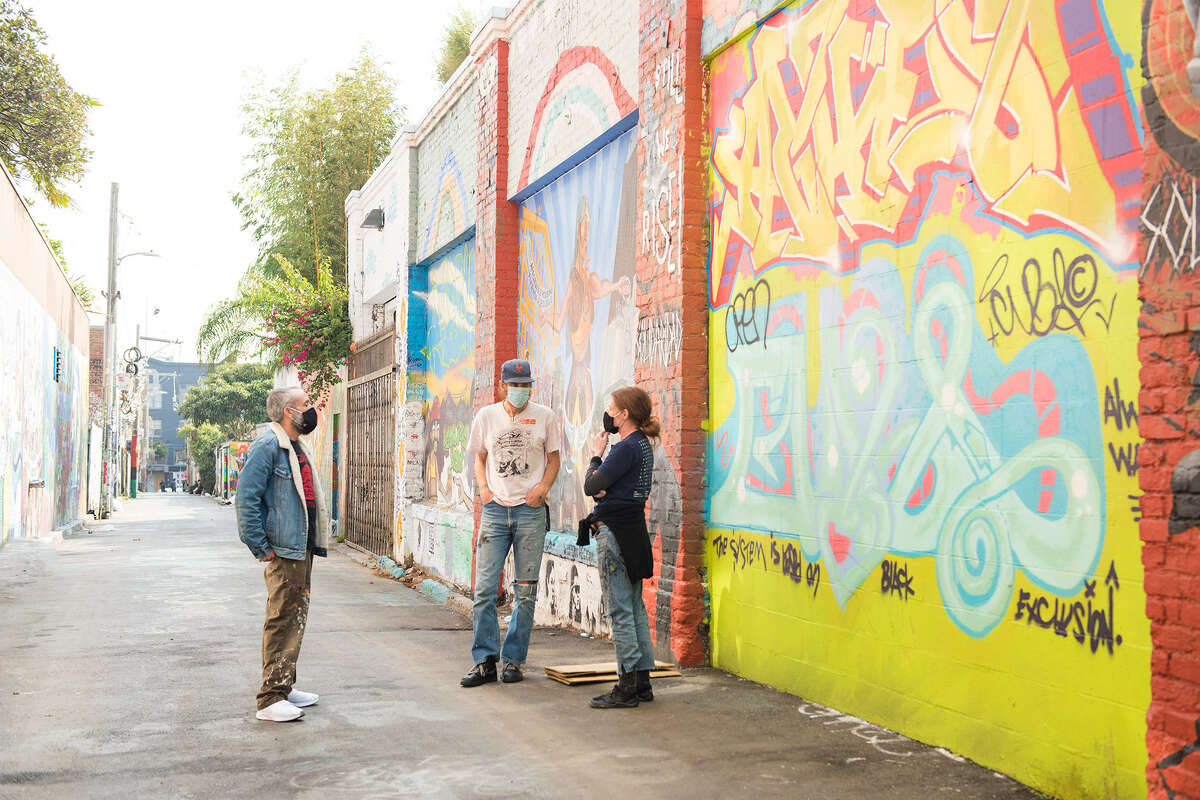 Community Thrift's interim executive director Brian Stump, center, chats with Clarion Alley Mural Project co-directors Christopher Statton, left, and Megan Wilson.
