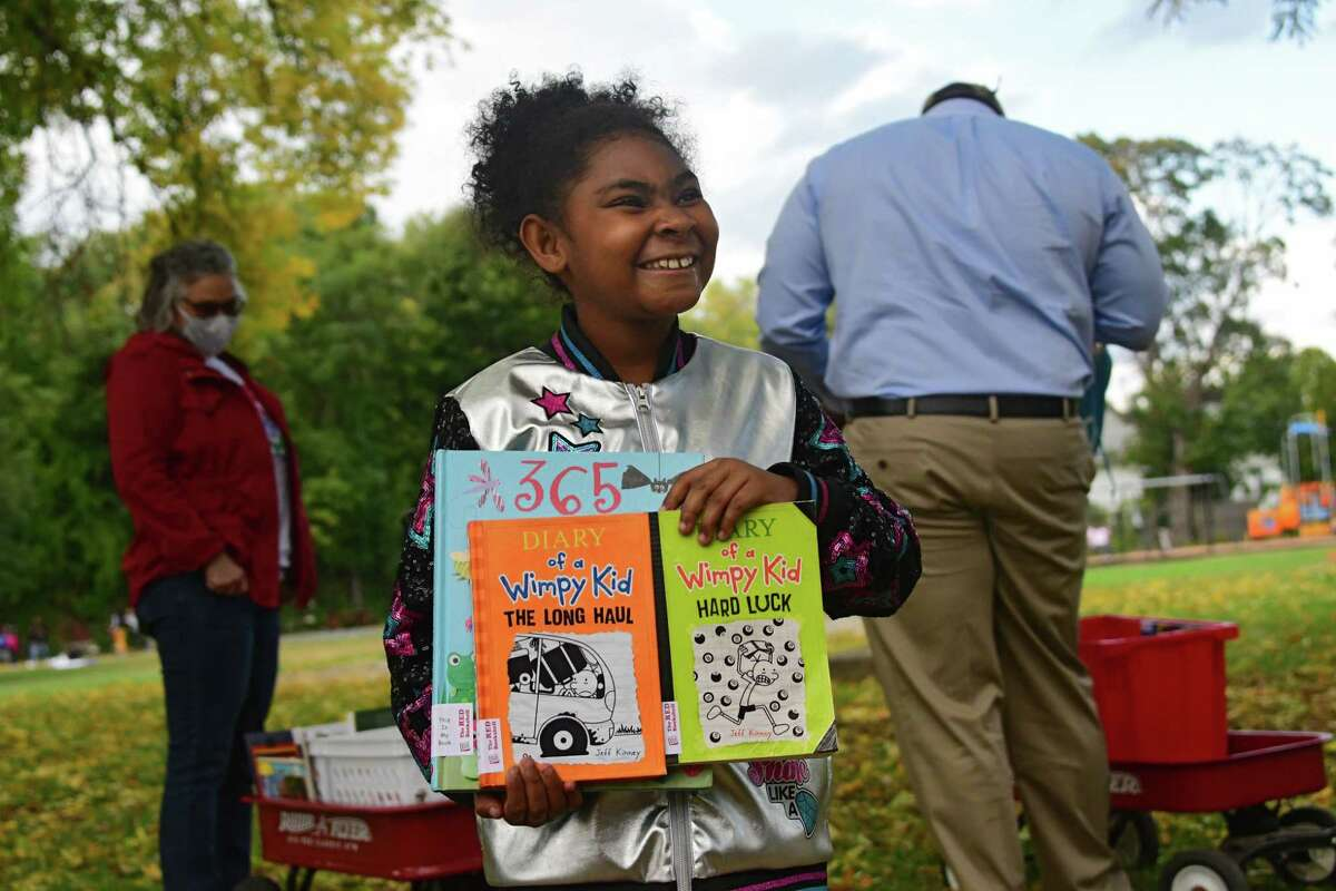 Azayvia Rivera, 8, of Albany shows her father what books she picked out from the RED Bookshelf at the Black Lives Matter Park on Monday, Oct. 5, 2020 in Albany, N.Y. (Lori Van Buren/Times Union)