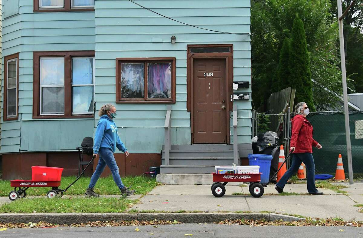 Rachel Eveleth, left, and Mary Beth Fowler who started The RED Bookshelf program pull wagons full of Children's books to give out to people down Third St. on Monday, Oct. 5, 2020 in Albany, N.Y. (Lori Van Buren/Times Union)