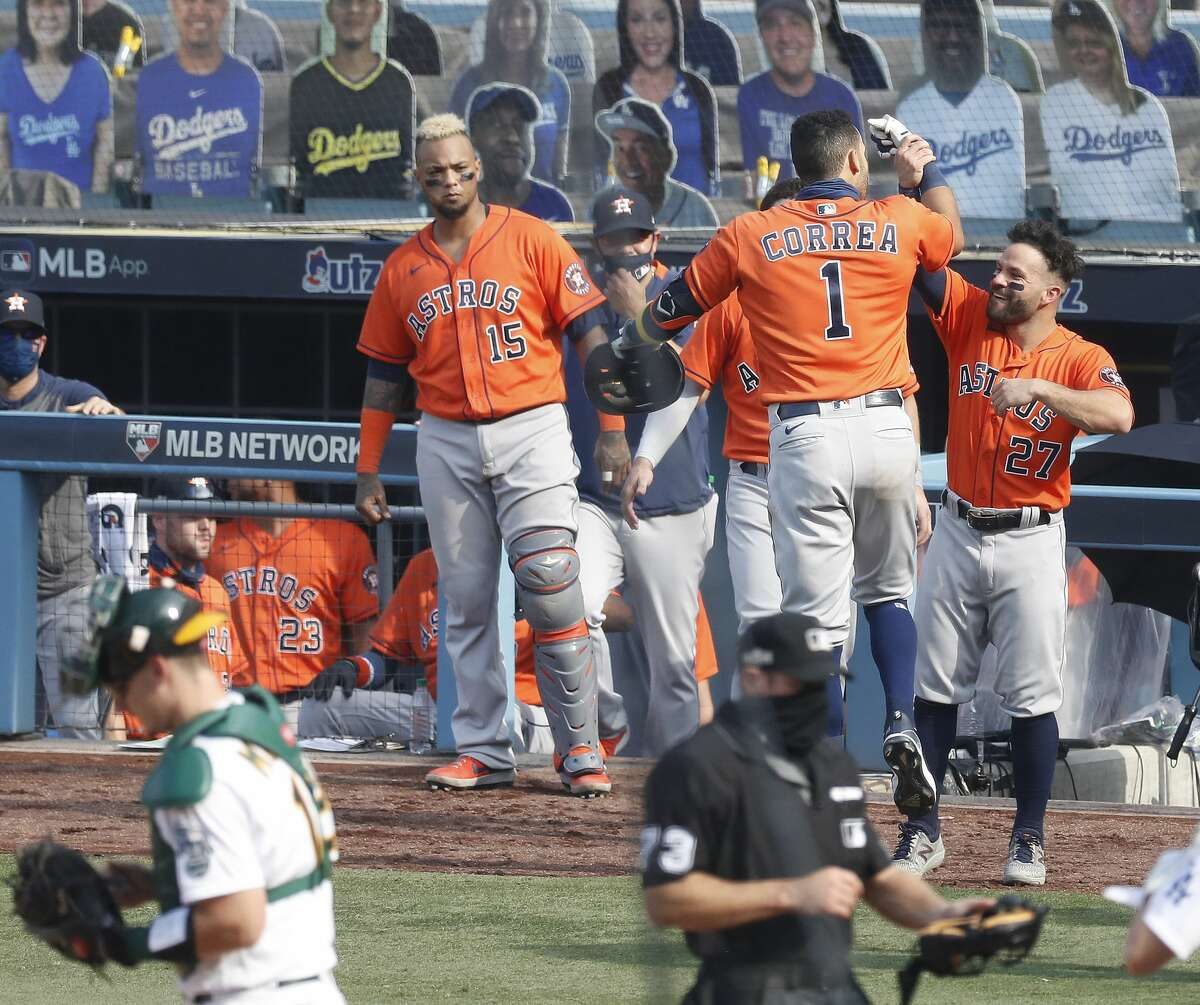 Houston Astros Carlos Correa celebrates with Jose Altuve after hitting his second home run of the day during the seventh inning of Game 1 of the American League Division Series, Monday, October 5, 2020, in Los Angeles, at Dodger Stadium.