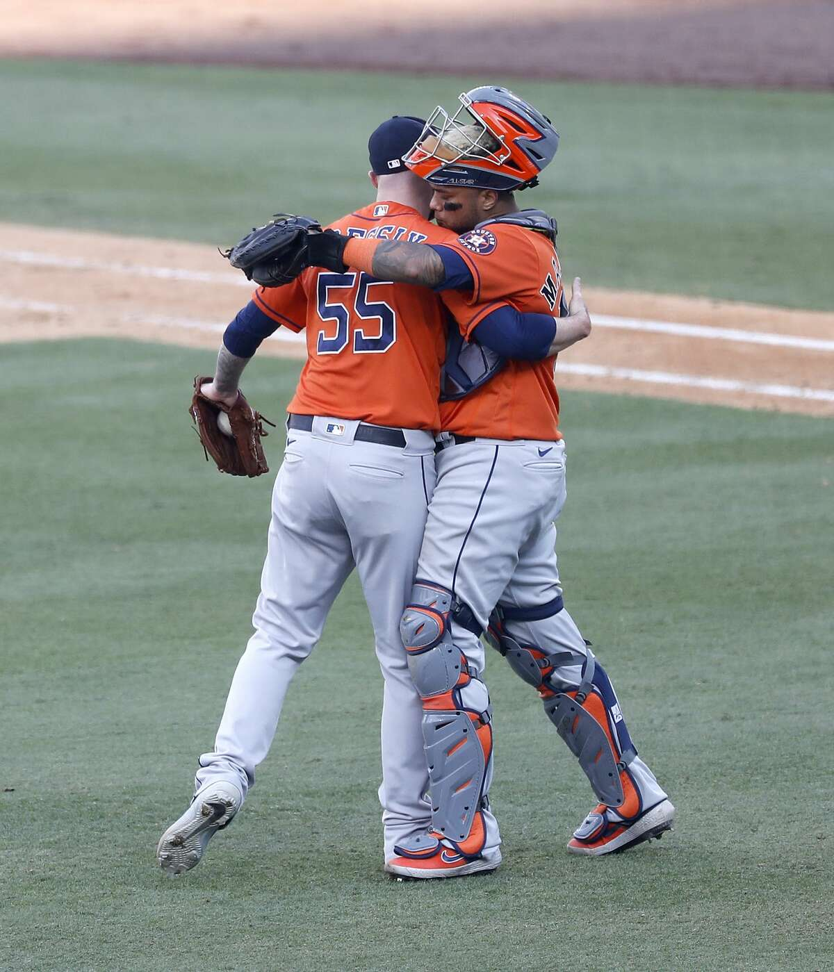 Houston Astros relief pitcher Ryan Pressly (55) hugs catcher Martin Maldonado (15) after Oakland Athletics Sean Murphy struck out swinging to end Game 1 of the American League Division Series, Monday, October 5, 2020, in Los Angeles, at Dodger Stadium. Astros won the game 10-5.
