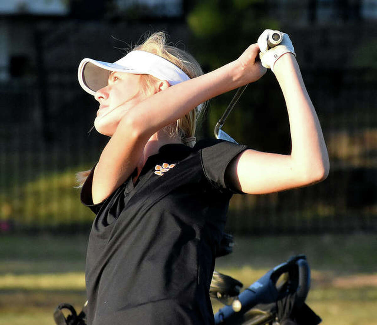 Edwardsville's Caitlyn Dicks eyes her shot as it heads towards the green on the third hole at Legacy Golf Course on Monday in Granite City.