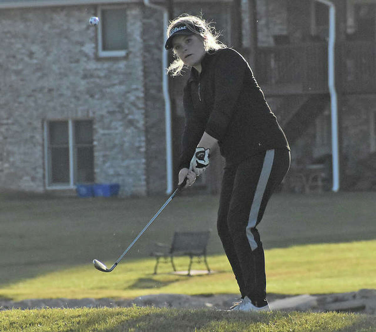 Edwardsville's Bailey Vorachek hits a chip shot onto the green on the seventh hole at Legacy Golf Course on Monday in Granite City.