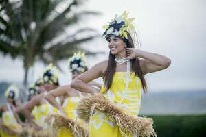 A group of women are doing a traditional Hawaiian dance during a luau for tourists on vacation.