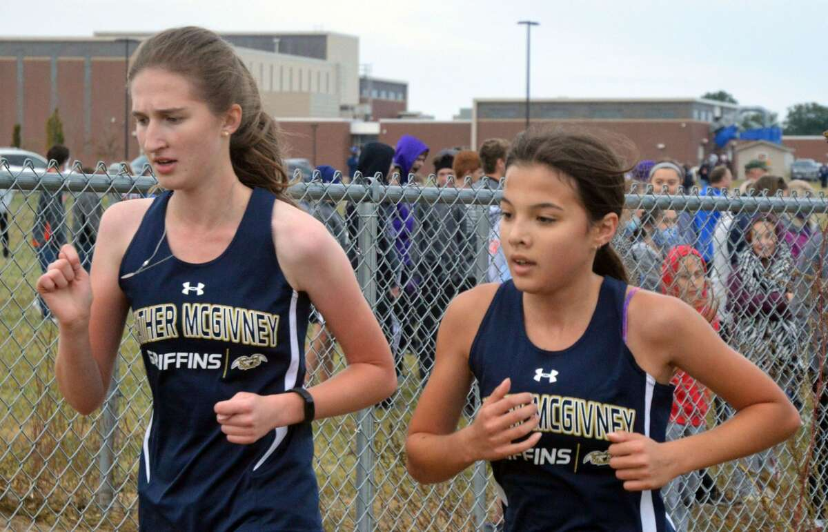 Father McGivney freshman Kaitlyn Hatley, right, and sophomore teammate Alyssa Terhaar compete in the Wesclin Invitational on Saturday.