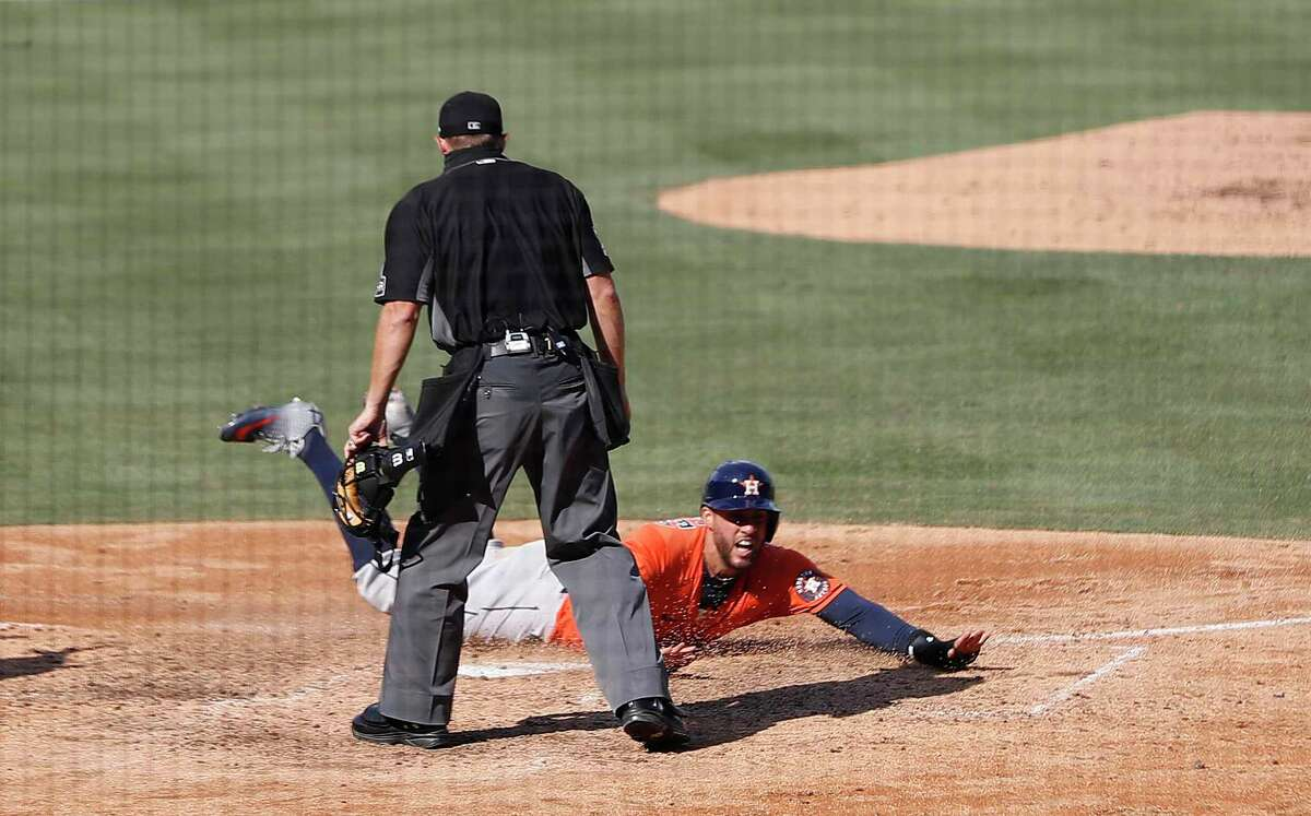 George Springer, who had four hits in Game 1 against the A's on Monday, slides home to score after a Jose Altuve double in the sixth.