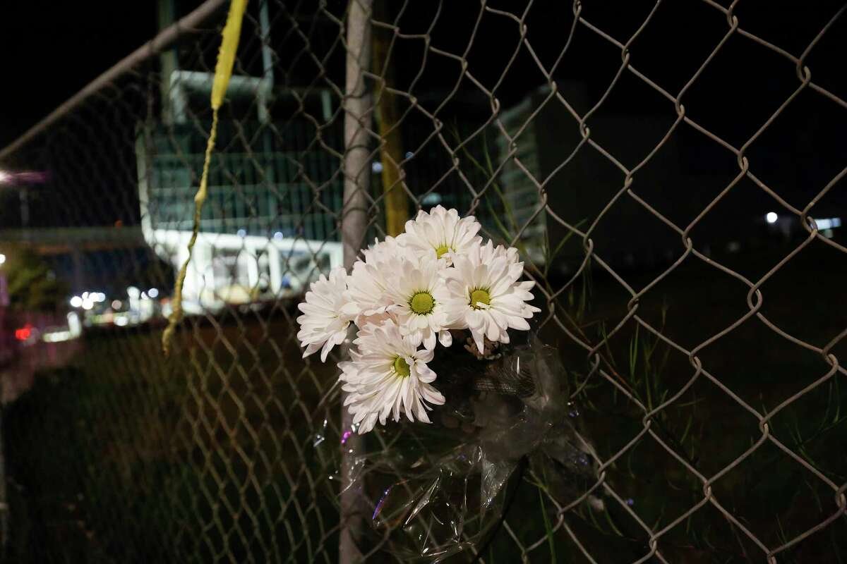 Flowers on a fence as crews work into the night in City Centre area of Houston following a building collapsing killing three on Monday, Oct. 5, 2020.