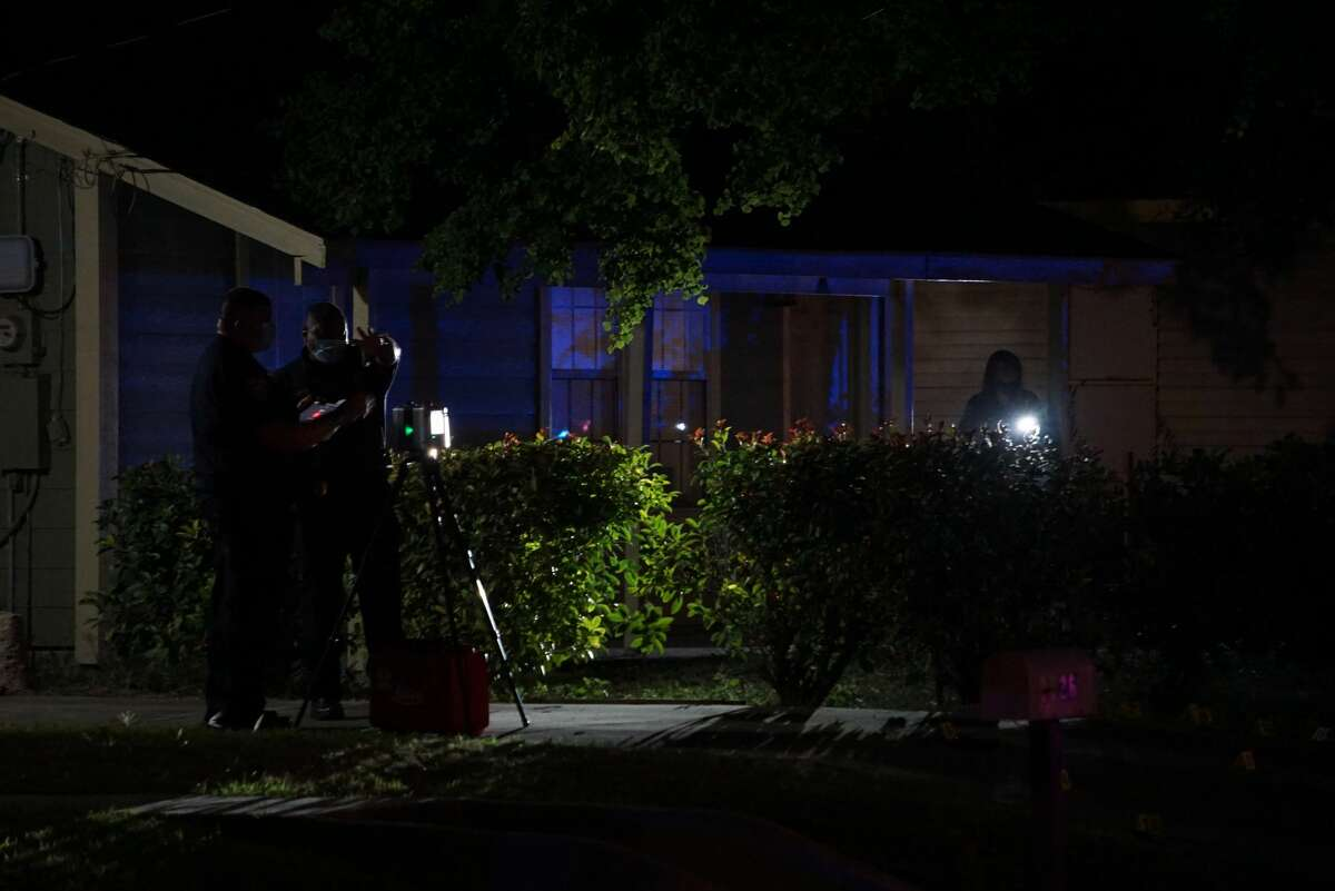 San Antonio Police examine the scene where a man was shot by police Monday evening after he fired an entire magazine at an officer but only hit his body camera at about 6:15 p.m. Monday, Oct. 5, 2020, at a home near the intersection of Logwood Avenue and Grosvenor Street.