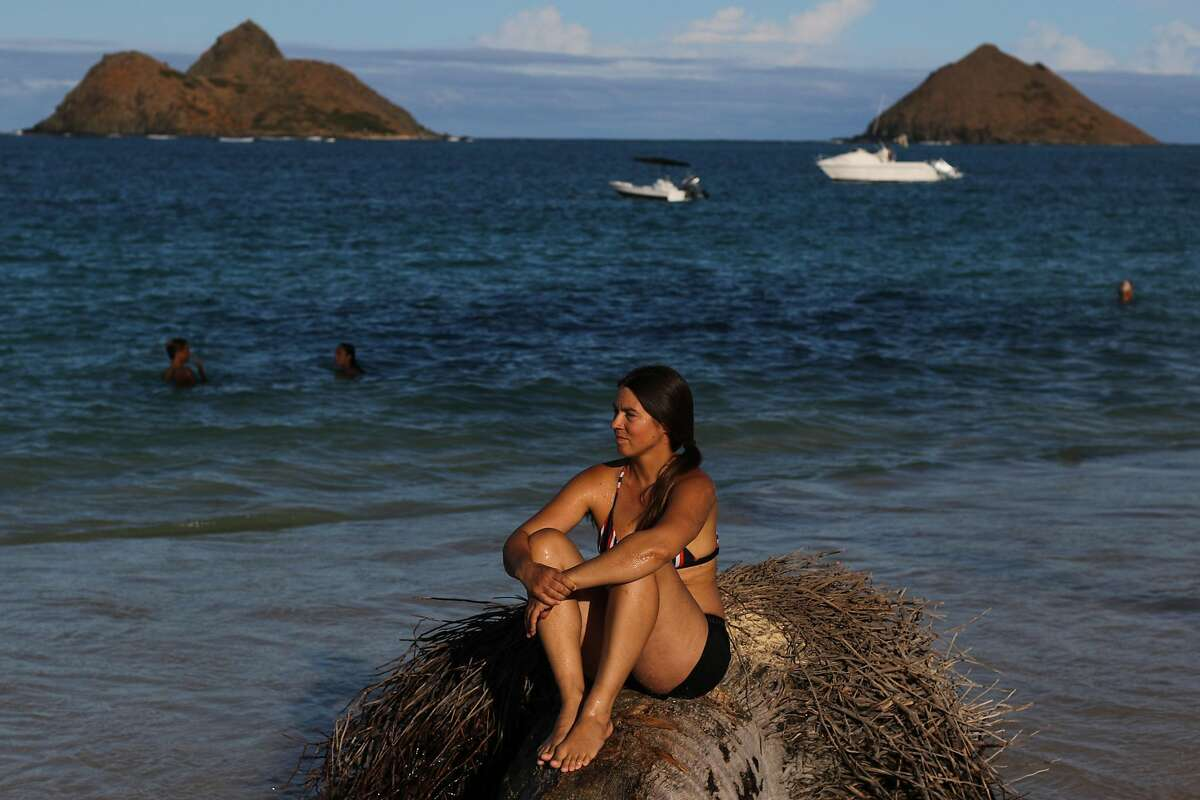 Rower Lia Ditton poses for a portrait sitting in a stagnant coconut tree timber on October 1, 2020 in Lanikai Beach, Kailua, HI.