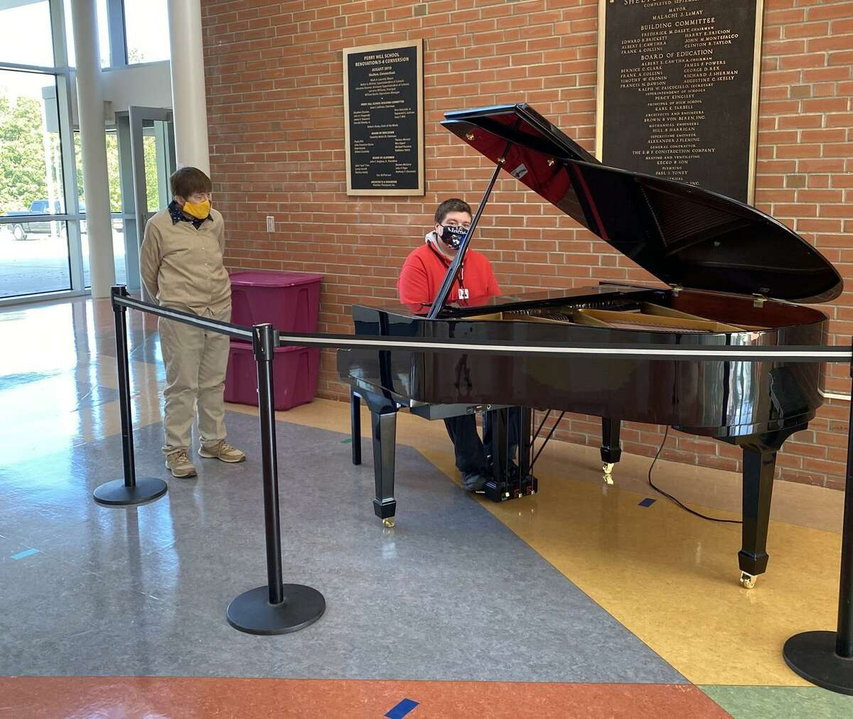 Perry Hill School music teacher Erik Rooney plays the newly donated piano as Deb Keller, PHS music teacher and K-12 music curriculum Leader, looks on. Keller spearheaded getting the piano.