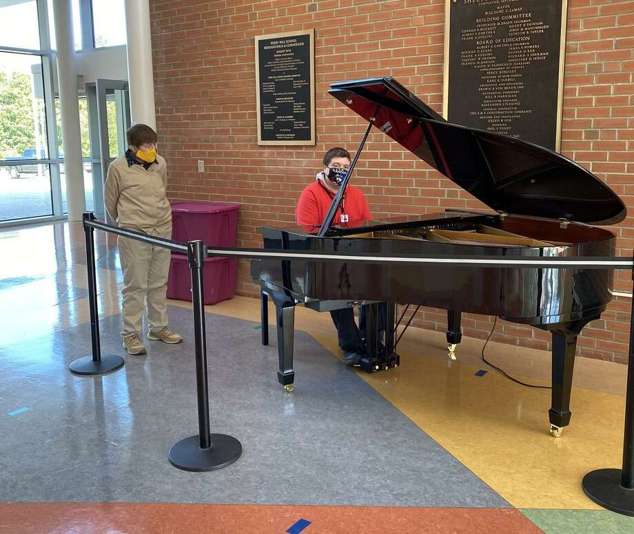 Perry Hill School music teacher Erik Rooney plays the newly donated piano as Deb Keller, PHS music teacher and K-12 music curriculum Leader, looks on. Keller spearheaded getting the piano. Photo: Perry Hill School / Contributed Photo / Connecticut Post
