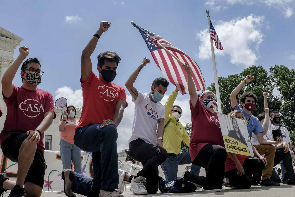 Demonstrators hold their fists in the air while kneeling outside the U.S. Supreme Court in Washington, D.C., U.S., on Thursday, June 18, 2020. A divided U.S. Supreme Court dealt a surprise blow to President Donald Trump, blocking him from ending the Obama-era program that shields 670,000 young undocumented immigrants from deportation and lets them seek jobs. Photographer: Alex Wroblewski/Bloomberg