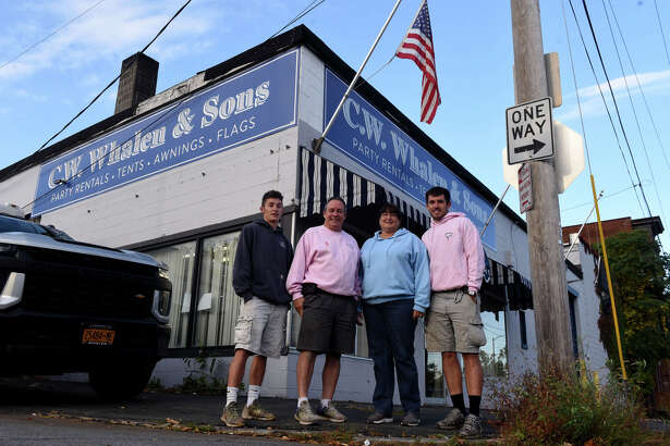 Cornelius Whalen Jr., second from left, is joined by wife, Tracy, and sons Matthew, left, Connor, right, outside their C.W. Whalen and Sons party equipment rental offices on Thursday, Oct. 1, 2020, on North Street in Troy, N.Y. (Will Waldron/Times Union)