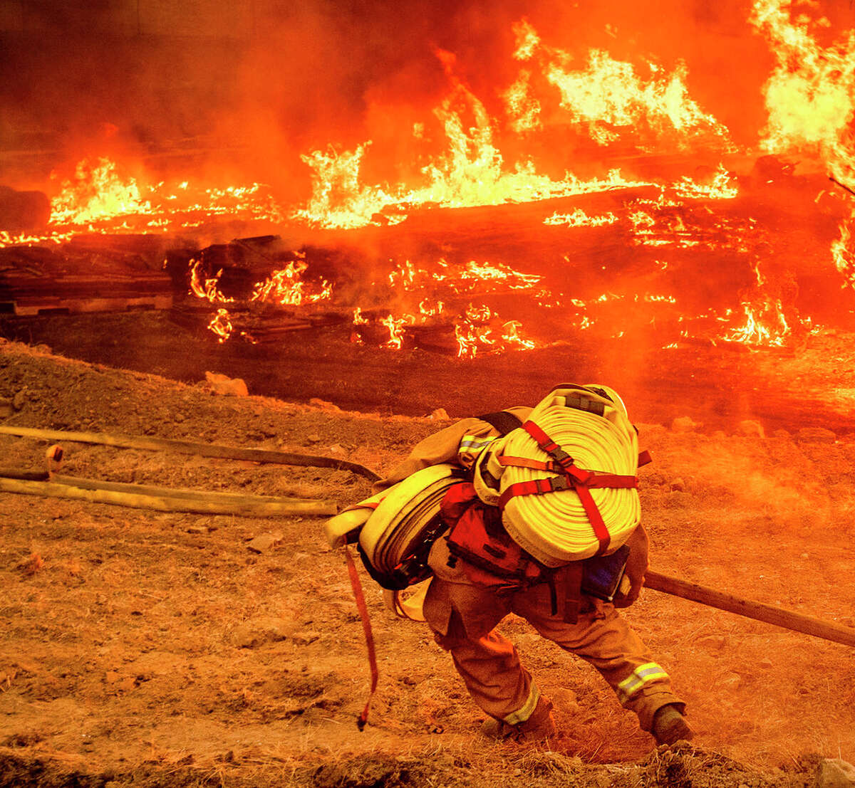 A firefighter carries a hose while battling the Glass Fire in a Calistoga, Calif., vineyard on Thursday, Oct. 1, 2020. (AP Photo/Noah Berger)