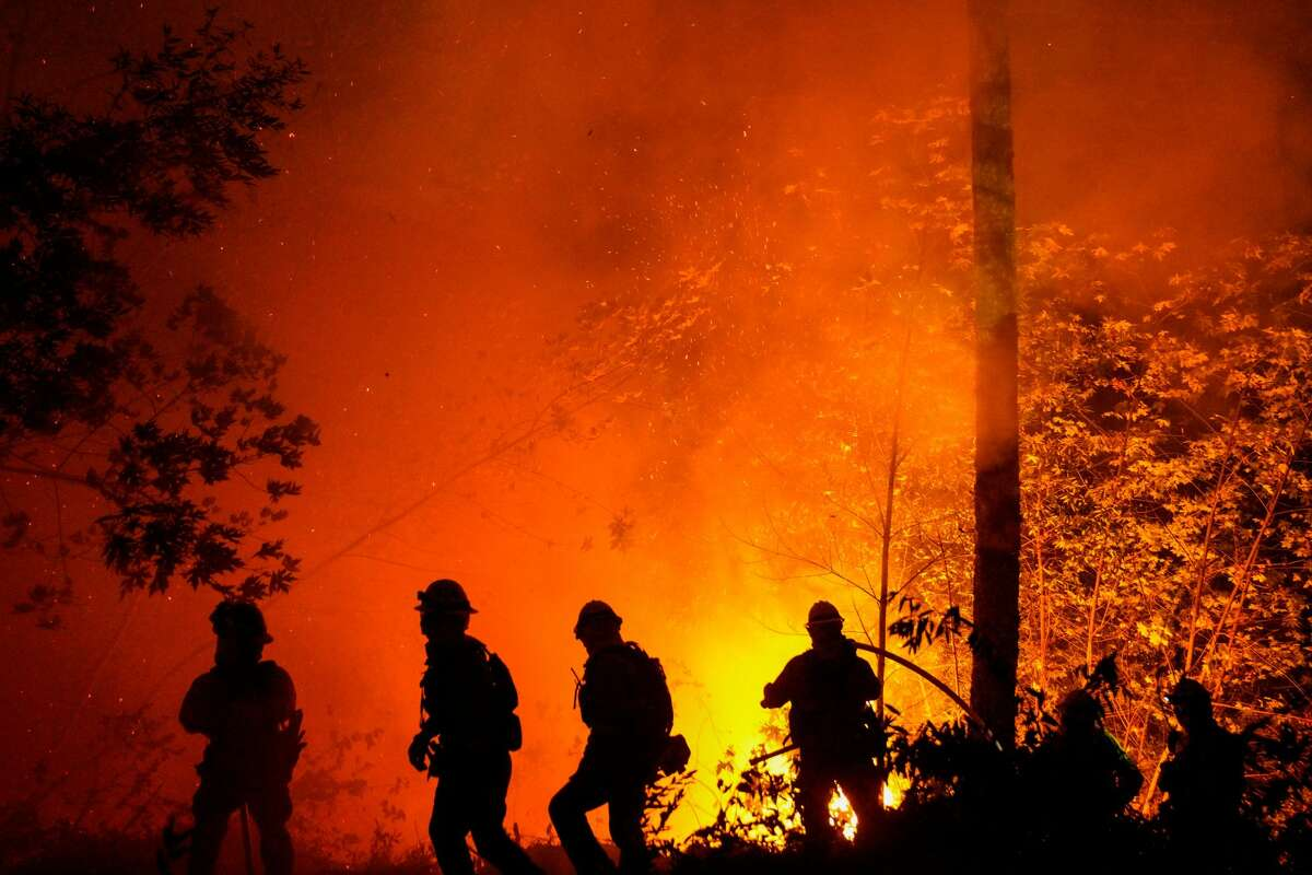 Firefighters perform structure protection against the Glass Fire in Napa County along CA-29 just past Old Lawley Toll Road on Thursday, Oct. 1, 2020, in Calistoga, Calif.