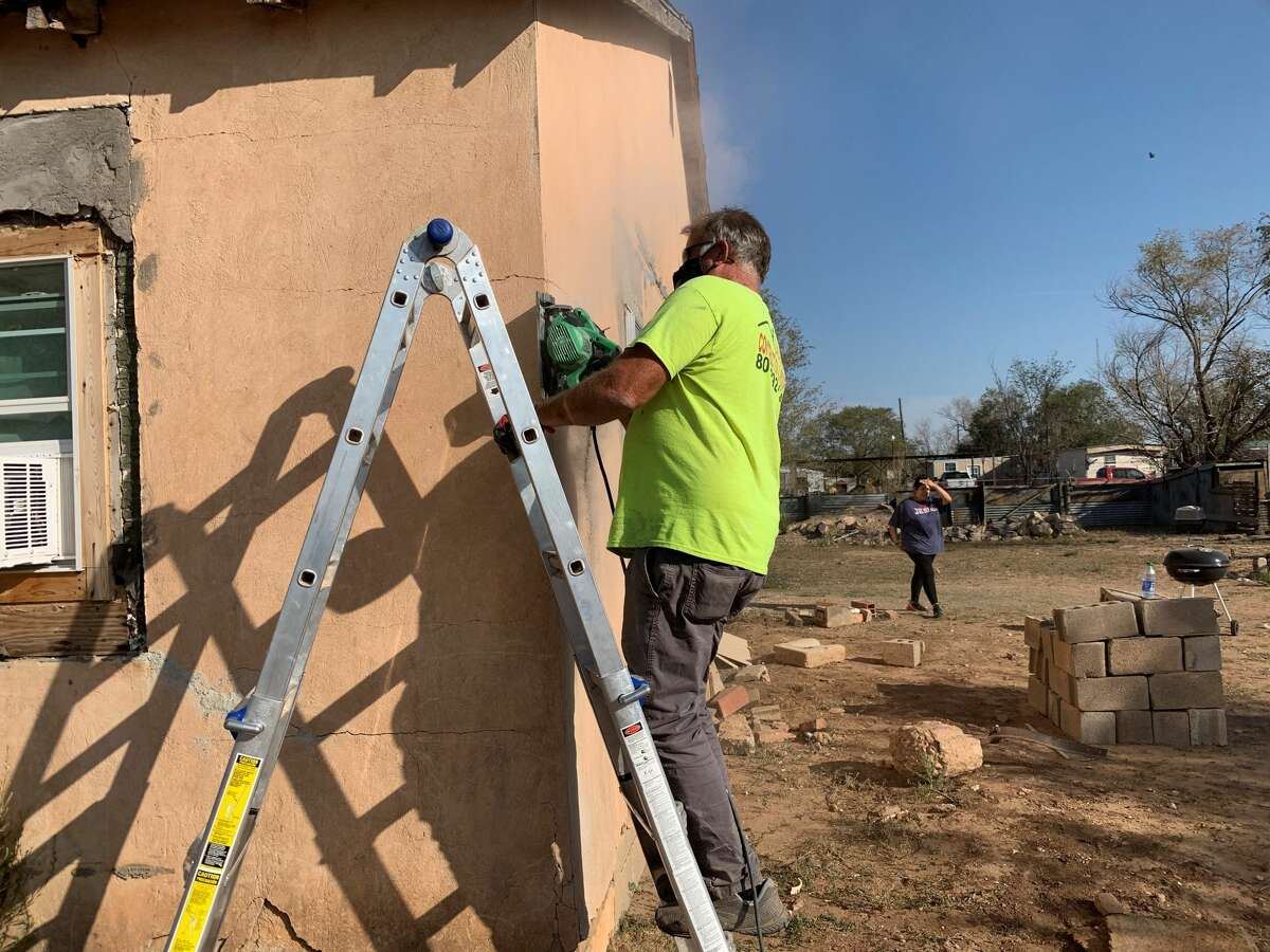 Local contractor Jack Wirth works on the exterior of a home in Seth Ward, preparing it for winterization. This is part of First Baptist Church of Plainview's Community Missions Projects.