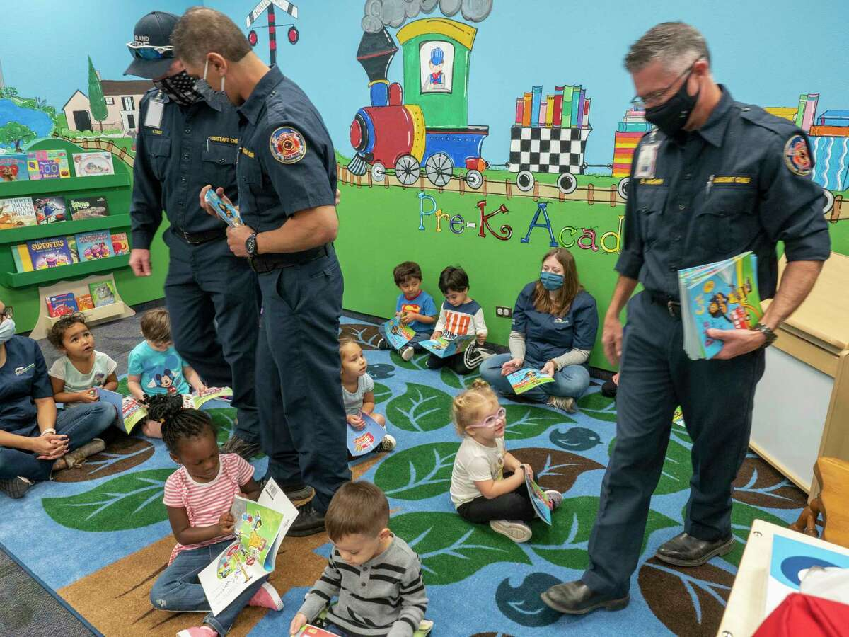 Midland Fire Department Asst. Chief Michael Tully, Asst. Chief Michael Cota and Asst. Chief Brian McGary hand out copies of the book Pete the Cat, Firefighter Pete, by James Dean, after reading the book 10/06/2020 morning to three-year-olds at Midland College Pre-K Academy. Tim Fischer/Reporter-Telegram