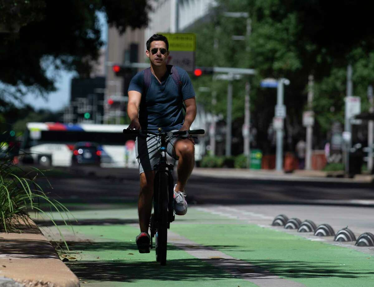 Drew Saenz takes advantage of the cool fall weather to bike on Lamar Street bike lane Wednesday, Sept. 30, 2020, in Downtown Houston.