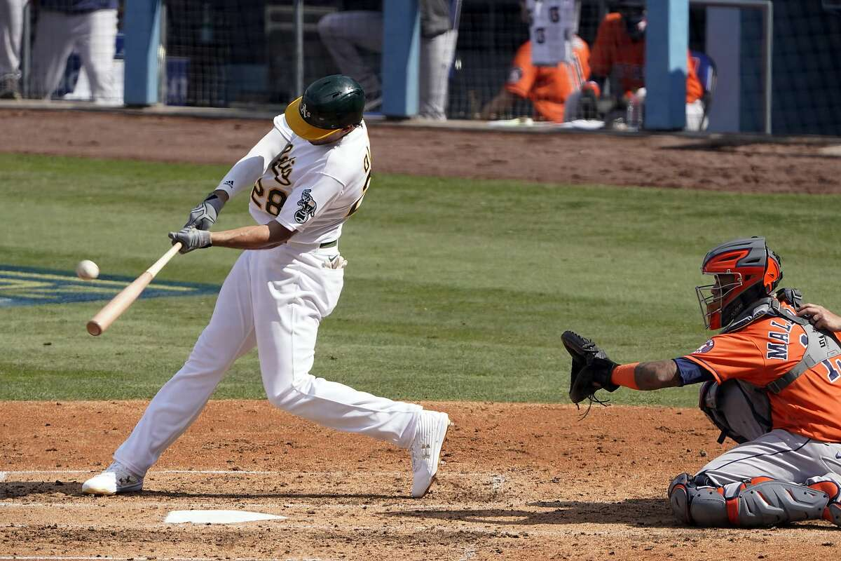 Oakland Athletics' Matt Olson (28) hits a solo home run in front of Houston Astros catcher Martin Maldonado during the fourth inning of Game 1 of a baseball American League Division Series in Los Angeles, Monday, Oct. 5, 2020. (AP Photo/Marcio Jose Sanchez)