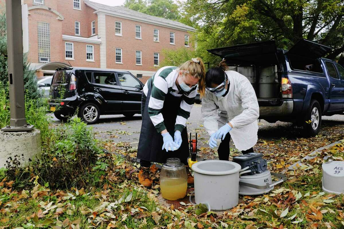 Siena College Environmental Studies students, junior Cassidy Hammecker, left, and senior Jennifer Guzman collect wastewater outside a dorm on Tuesday, Oct. 6, 2020, in Loudonville, N.Y. The college is testing the wastewater from dorms on a weekly basis to monitor for COVID. (Paul Buckowski/Times Union)
