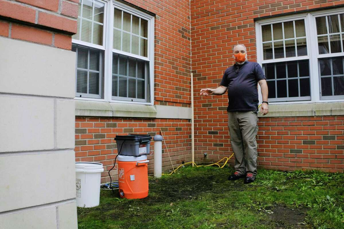John Cummings, dean of the School of Science at Siena College, talks about a dedicated wastewater sampler outside a dorm on Tuesday, Oct. 6, 2020, in Loudonville, N.Y. Cummings said he built the sampler as a mashup of different ideas he read about. The sampler is built using a pool pump, insulated liquid cooler, tubing, and a gallon glass container. The college is testing the wastewater from dorms on a weekly basis to monitor for COVID. (Paul Buckowski/Times Union)