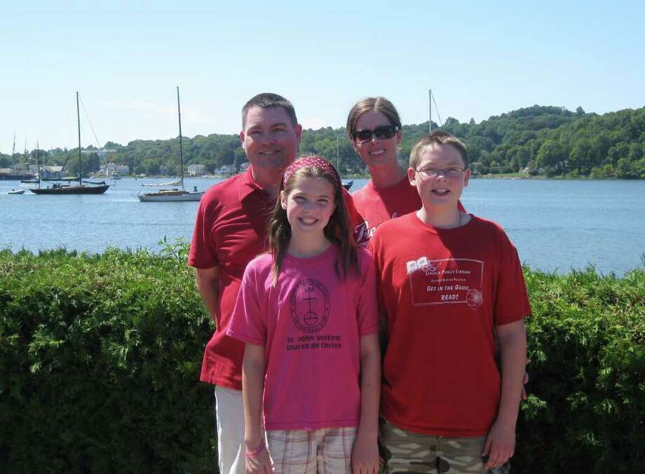 Mike Grenier (top left) stands with wife Sheri, daughter Chloe, 10 and son, Levi, 13, stands in front of Sea View Snack Bar on Greenmanville Avenue near Mystic Seaport. The Greniers, who hail from Illinois, are traveling the country trying to get as many people as possible to register as organ donors. Mike Grenier is a donation recipient. Last week, the family arrived in Connecticut, where they plan to stay until Wednesday. Photo: Contributed Photo / Connecticut Post Contributed