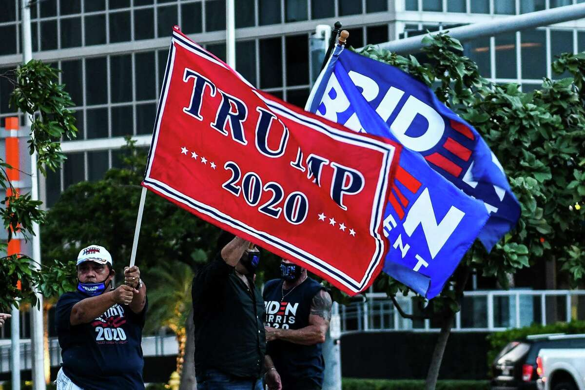 Supporters of US President Donald Trump and Democratic presidential nominee and former Vice President Joe Biden wave flags prior to Biden's arrival for an NBC townhall outside of the Perez Art Museum in Miami, Florida on October 5, 2020.