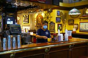 BOSTON, MA - JULY 1: Eliana Barros, a bartender/server in Cheers, finishes a drink order at Quincy Market in Boston on July 1, 2020. Some of the retail/restaurant tenants in Faneuil Marketplace re-open July 1, during the coronavirus pandemic. They are in a dispute with commercial landlords over back rent. (Photo by Pat Greenhouse/The Boston Globe via Getty Images)