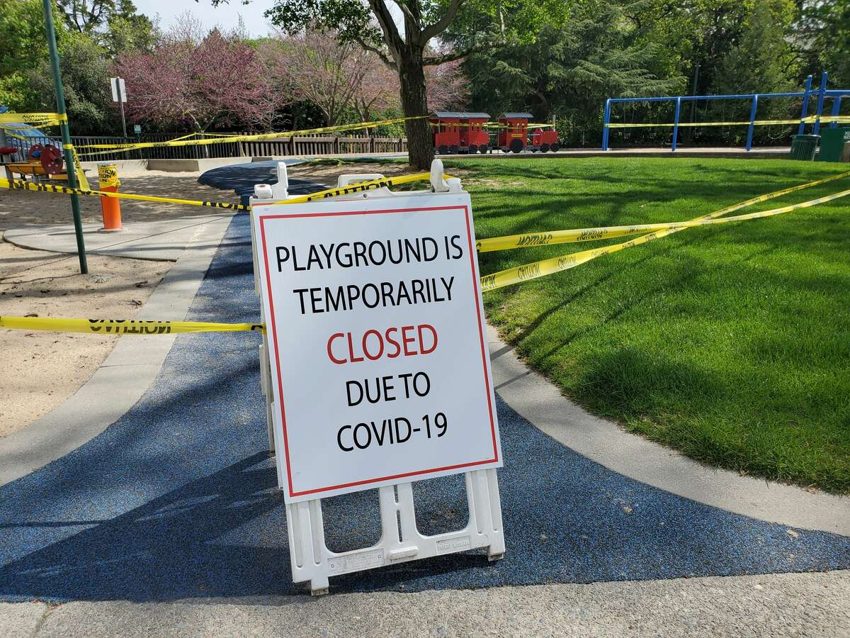 FILE - Caution tape and signs are visible at a closed playground during an outbreak of COVID-19 coronavirus in Walnut Creek, California, April 8, 2020.