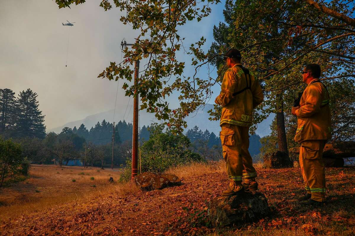 (L-r) Firefighters Scott Sousa and Dave Novelli watch a helicopter drop over the Glass Fire off of Highway 29 on Sunday, Oct. 4, 2020 in Calistoga, California.