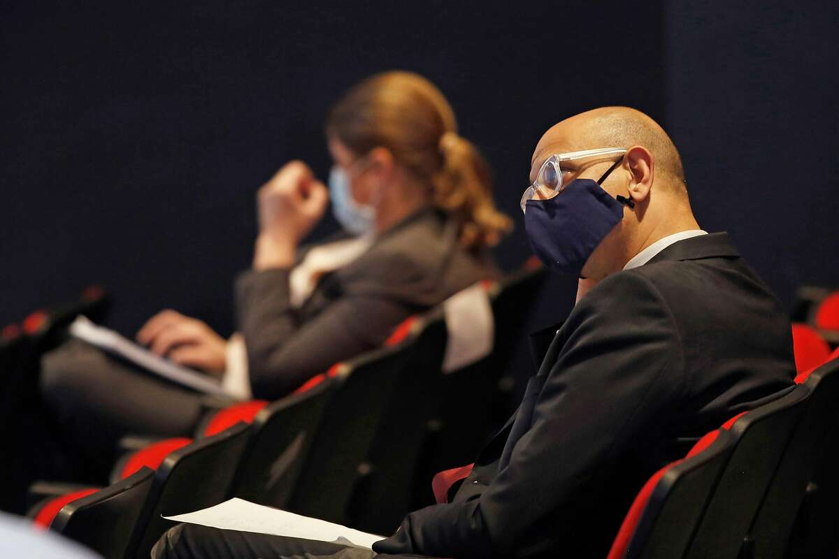 California Health and Human Services Secretary Dr. Mark Ghaly wears a face mask as he listens to Gov. Gavin Newsom at a news conference in Sacramento on May 14, 2020.