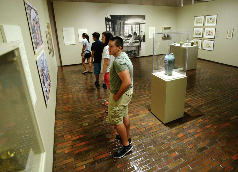 """Christian Fuselier, 16, and others look at pieces in the """"Women, Art and Social Change: The Newcomb Pottery Enterprise"""" exhibit at the Stark Museum on Saturday. The Stark Museum of Art in Orange participated in the Smithsonian Day event Saturday, granted those with tickets printed from the Smithsonian magazine free admission to the grounds. The event coincided with a new exhibit from the Smithsonian, """"Women, Art and Social Change: The Newcomb Pottery Enterprise.""""  Photo taken Saturday 9/27/14  Jake Daniels/@JakeD_in_SETX Photo: Jake Daniels / ©2014 The Beaumont Enterprise/Jake Daniels"""