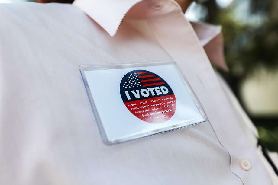"""A voter wears an """"I Voted"""" badge after casting their ballot in a mail-in ballot drop box outside of a library Oct. 5, 2020, in California. Photo: Mario Tama / Getty Images"""