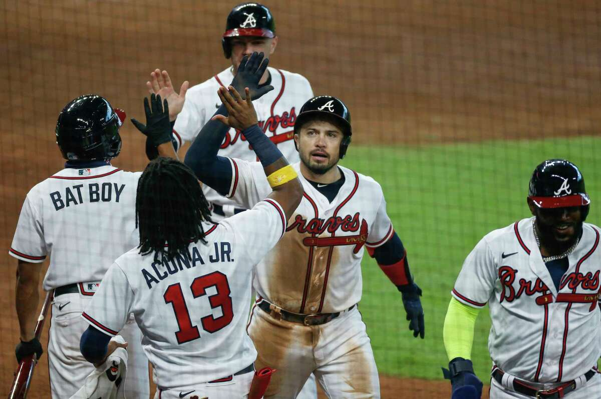 Atlanta Braves catcher Travis d'Arnaud (16) celebrates with teammates after hitting a three-run home run against the Miami Marlins, giving them the lead, during the seventh inning in Game 1 of the National League Division Series at Minute Maid Park on Tuesday, Oct. 6, 2020, in Houston.