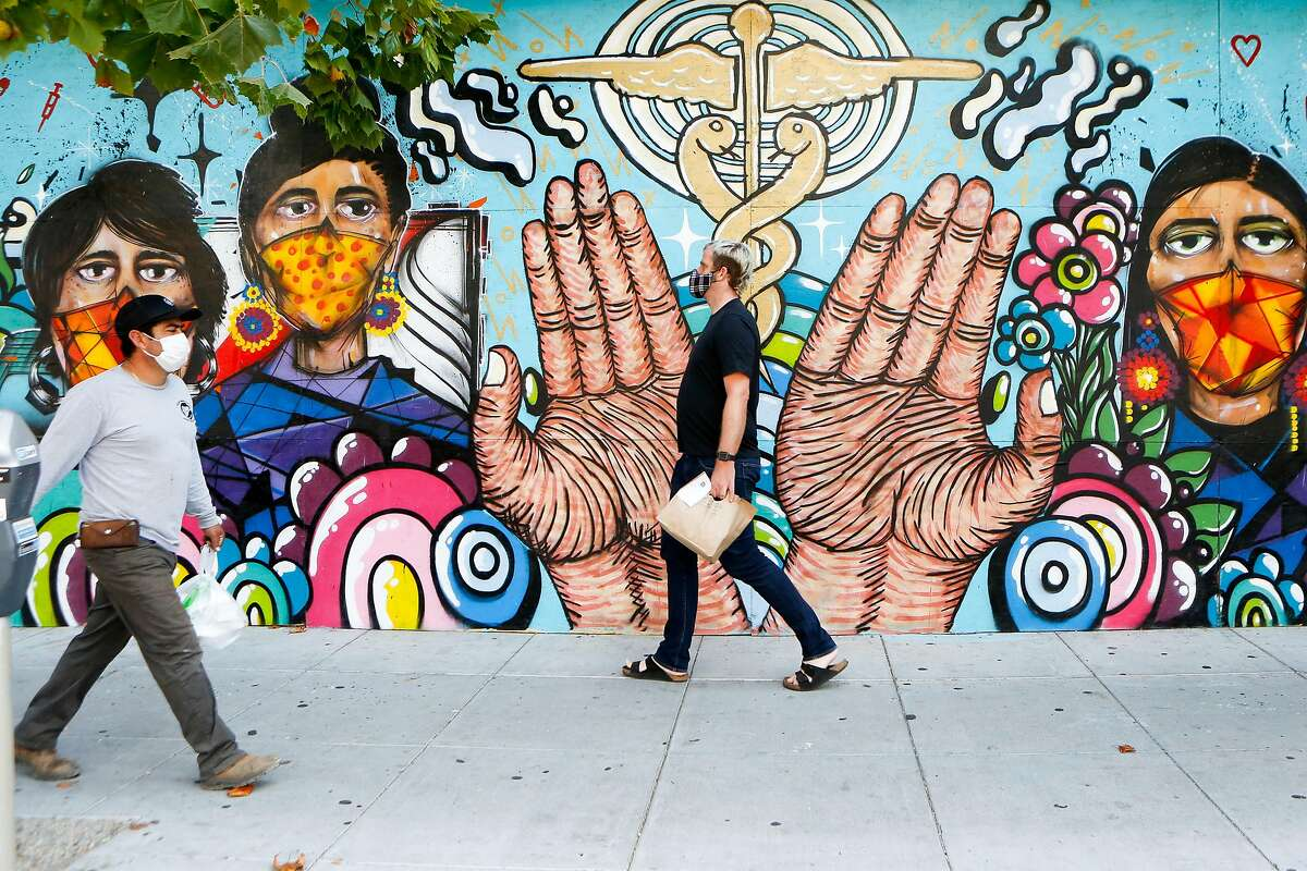 People pass a coronavirus mural at Sutter Pacific Medical Foundation on Valencia Street in S.F. last month. All Bay Area counties are infections rates climb.
