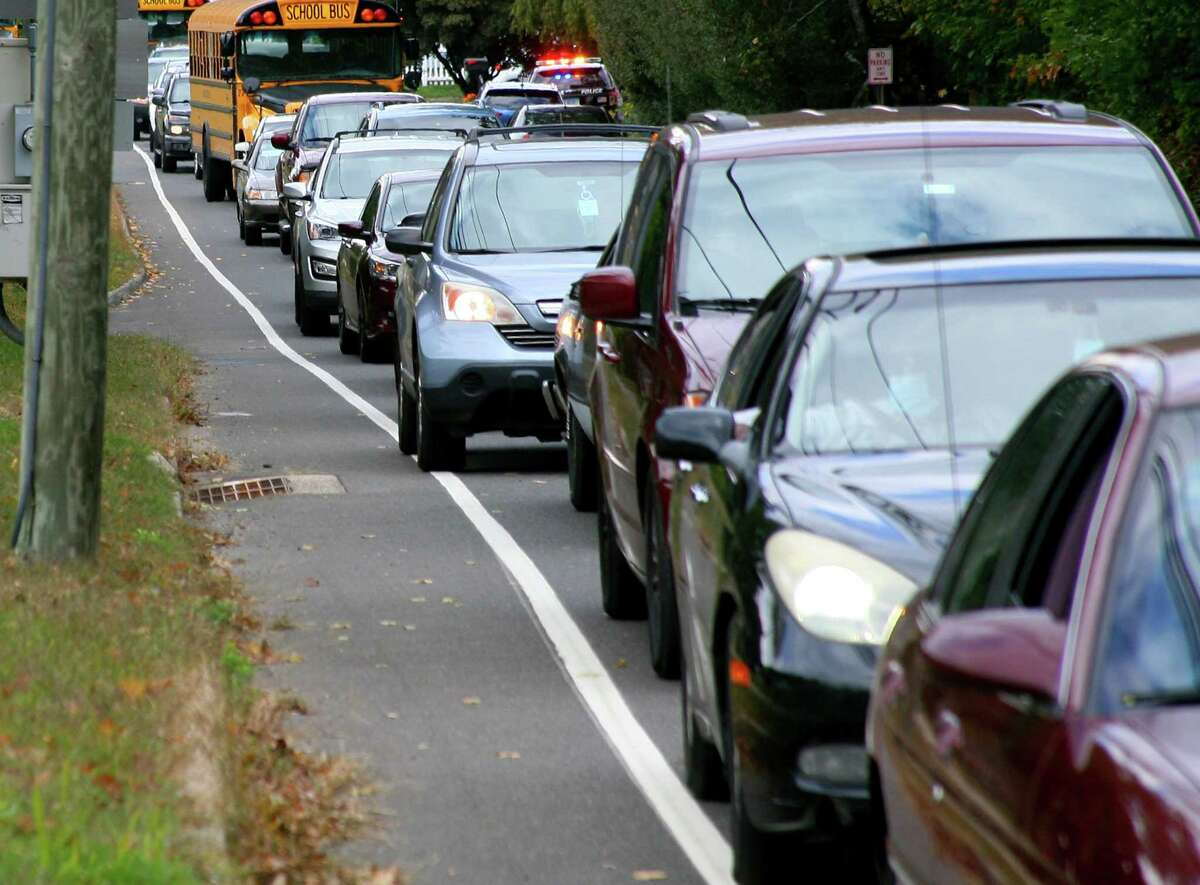 Vehicles back up along Wakelee Avenue to enter the Nolan Field parking lot to receive food packages in Ansonia, Conn., on Tuesday Oct. 6, 2020. Farmers to Family arranged the free food distribution for valley families. Each family will receive 12 pounds of produce, 5 pounds of meat, 5 pounds of dairy and a gallon of milk. About 1,200 boxes were given out.