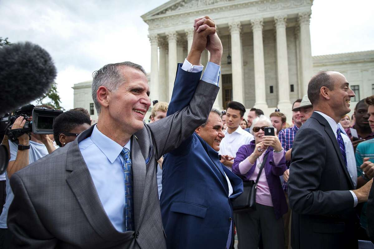 FILE -- Gregory Bourke, left, and his husband, Michael DeLeon, right, plantiff's in one of the U.S. Supreme Court's same-sex marriage cases, outside the court following the the ruling in their case, in Washington, June 26, 2015. Justices Clarence Thomas and Samuel A. Alito Jr., who dissented from the Supreme Court's 2015 decision establishing a constitutional right to same-sex marriage, appeared to urge the court on Monday, Oct. 5, 2020, to reconsider the ruling, which they said had invented a right with no basis in the text of the Constitution. (Doug Mills/The New York Times)