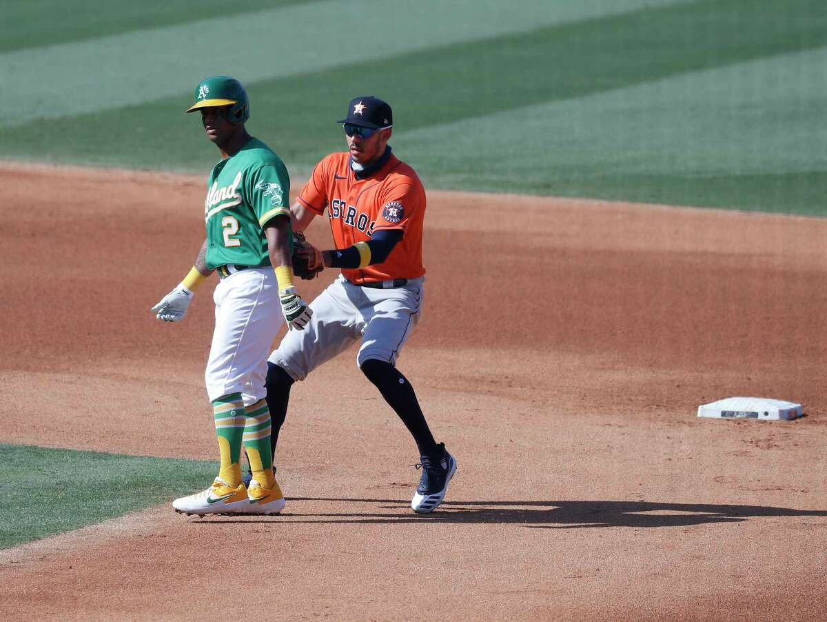 Astros shortstop Carlos Correa tags Athletics runner Khris Davis on a double play to end the fourth inning of Game 2 of the American League Division Series on Tuesday. Davis had represented the potential tying run.